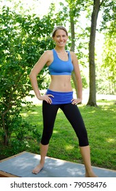 Beautiful young woman in park preparing to enter a yoga pose (asana) and smiling