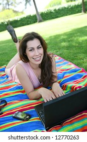 A beautiful young woman in the park working on laptop computer