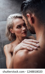 beautiful young woman passionately looking at man in shower