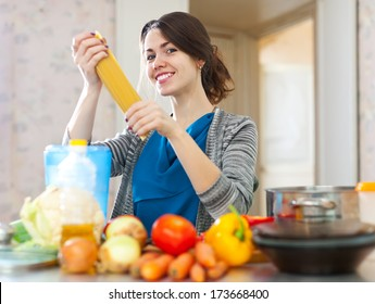 beautiful young woman with pasta and vegetables at her kitchen  at home