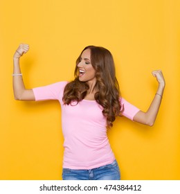 Beautiful young woman in pastel pink shirt and jeans holding arms outstretched, flexing muscles, shouting and looking away. Waist up studio shot on yellow background.