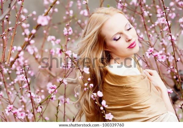 Beautiful young woman in peach garden