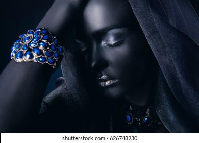 Beautiful young woman with perfect black skin wearing beautiful bracelet with precious stones and black veil. Jewelry and bijouterie. Body painting project. African style.