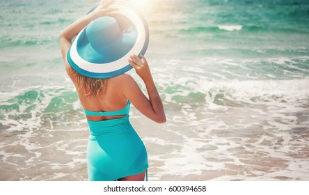 Beautiful young woman with perfect body on the beach in fashion swinsuit and hat.