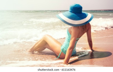 Beautiful young woman with perfect body on the beach in fashion swimsuit and hat.
