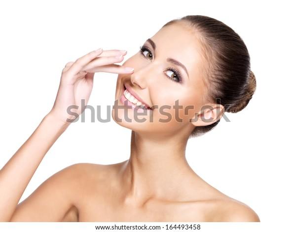 白い背景に完璧な清潔な肌を持つ美しい若い女性が鼻に触れ、にこにこ笑みを浮かべている