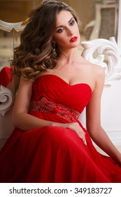 Beautiful young woman with perfect make up and hair style in gorgeous red evening dress in expensive luxury interior