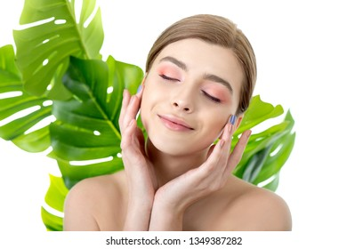 Beautiful young woman with perfect skin and natural make up posing front of plant tropical green leaves background. Teen model are of her face and body. SPA, wellness, bodycare and skincare.