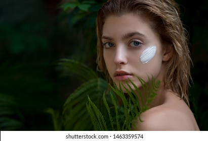 Beautiful young woman with perfect skin applies a facial cream front of plant tropical green leaves background with fern. SPA, wellness, bodycare and skincare.  Close up, selective focus.