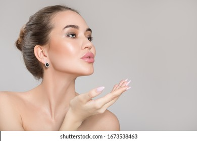 Beautiful young woman with perfect skin and make-up sends a kiss. Clean skin concept