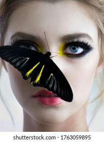 Beautiful young woman with perfect skin and bright yellow make up posing with butterfly on her face. Fashion beauty model with color professional makeup. SPA, wellness, make-up and skincare concept.