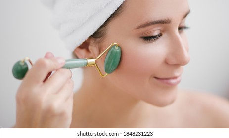 Beautiful young woman with perfect skin wearing towel on head using a jade face roller with natural quartz stones on white background.