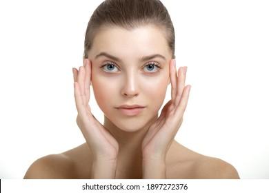 Schöne junge Frau mit perfekter Haut berührt ihr Gesicht. Porträt von lächelndem Schönheitsmodell mit natürlichem Make-up Sorge um ihre Haut. Spa, Hautpflege und Wellness.