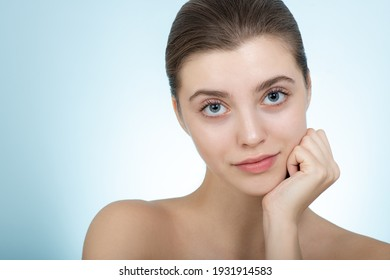 Beautiful young woman with perfect skin looks to the camera. Portrait of smiling beauty model with natural makeup caring about her skin. Spa, skincare and wellness.