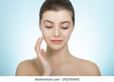 Beautiful young woman with perfect skin and closed eyes touches her face. Portrait of smiling beauty model with natural makeup caring about her skin. Spa, skincare and wellness.