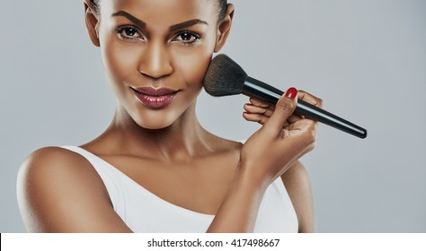 Beautiful young woman with perfect skin applying makeup with a brush against a gray background