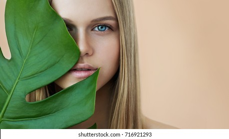 Beautiful young woman with perfect skin and natural make up. Teen model with green leaves. SPA,  skincare and wellness. Close up, selective focus.