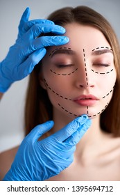 Beautiful young woman with perforation lines on her face before plastic surgery operation. Beautician hands in gloves touching woman face. Puncture lines on pure female skin. Surgeon measures face.