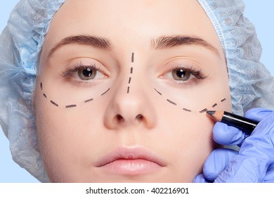 Beautiful young woman with perforation lines on her face before plastic surgery operation. Beautician touching woman face and draws a pencil or marker.
