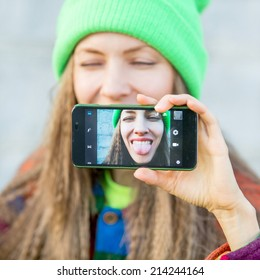 Beautiful young woman photographing herself with phone. Cute smiling young caucasian teenage girl taking a selfie outdoors. daylight