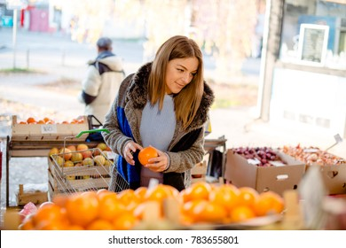 Beautiful young woman picking orange in greengrocer's shop, holding orange and basket.