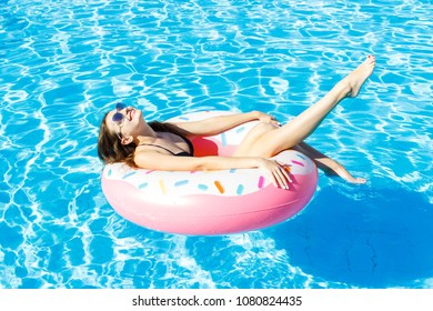 Beautiful young woman with pink circle relaxing in blue swimming pool.