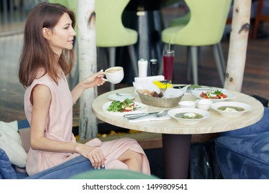 beautiful young woman in a pink dress has lunch in a restaurant. A dish with salad on the table. Girl is holding cup of cappuccino