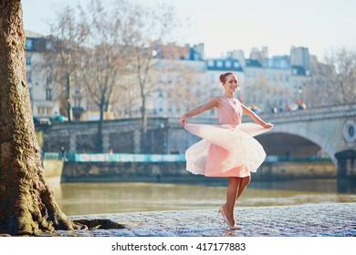 Beautiful young woman in pink dress dancing in Paris near the river Seine