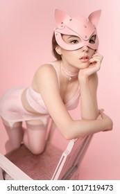 Beautiful young woman in pink lingerie and cat mask posing on chair against pink background