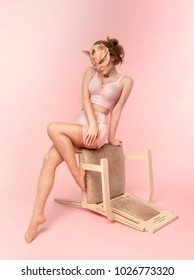 Beautiful young woman in pink lingerie and cat mask sitting on chair against pink background