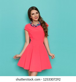 Beautiful young woman in pink mini dress and colorful braided necklace. Three quarter length studio shot on turquoise background.