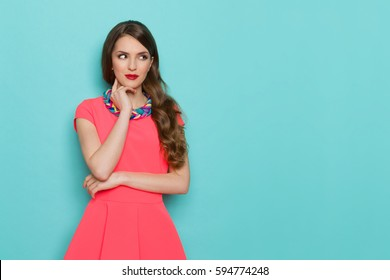 Beautiful young woman in pink mini dress and colorful braided necklace holding hand on chin and looking away. Three quarter length studio shot on turquoise background.