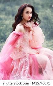 beautiful young woman in pink princess dress outdoor