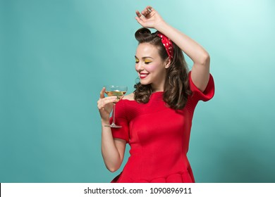 Beautiful young woman with pinup make and hairstyle at studio. Happy, smiling and pretty female caucasian model in retro or vintage style with a glass of champagne. Human emotions and facial