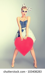 Beautiful young woman with pin-up make-up and hairstyle posing in studio with red hearts.