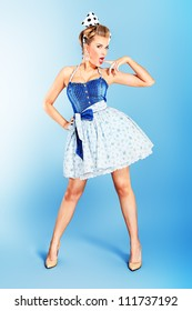 Beautiful young woman with pin-up make-up and hairstyle posing in studio.