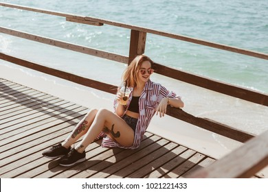 beautiful young woman with plastic cup sitting on wooden pier in front of sea