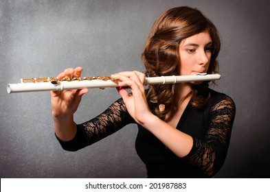 Beautiful young woman playing flute in studio. Alluring flutist in black evening dress with hairstyle makeup posing with flute on gray background