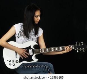 Beautiful young woman playing the guitar