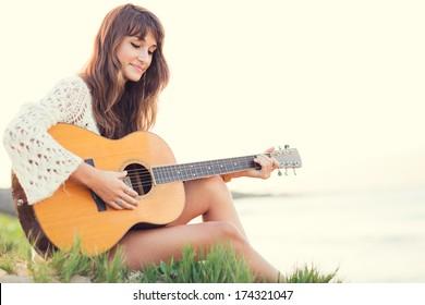 Beautiful young woman playing guitar on beach at sunset, fashion lifestyle