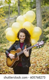 Beautiful young woman playing guitar on forest with yellow balloons. Girl wearing black jacket, fashion lifestyle.