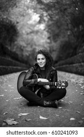 Beautiful young woman playing guitar sitting on the forest. Girl wearing black jacket and sunglasses, fashion lifestyle. Image in black and white.