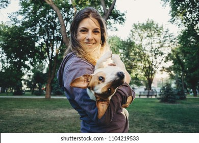 Beautiful young woman playing with her jack russell terrier dog in the park. Pets, care, domestic animals, happiness, friendship, trust, love, human and animals concept