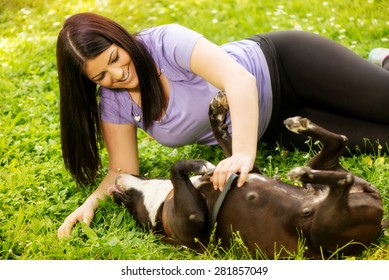 Beautiful young woman playing with her cute stafford terrier in the park.