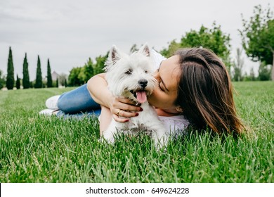 Beautiful young woman playing with her little west highland white terrier in a park outdoors. Lifestyle portrait.