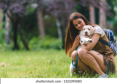 Beautiful young woman playing with a puppy labrador in the park