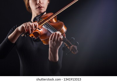 Beautiful young woman playing the violin against a dark background. Focus on violin