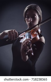 Beautiful young woman playing the violin against a dark background