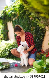 Beautiful young woman plays with puppy in garden