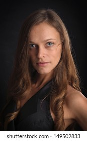 Beautiful young woman portrait. Dark background